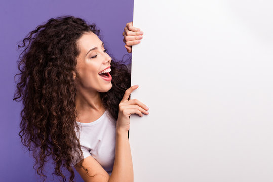 Close-up portrait of nice cute attractive charming cheerful cheery brunette wavy-haired lady showing looking aside large ad advert isolated over bright vivid shine violet purple background
