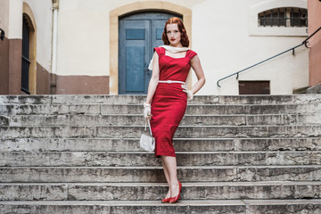 red haired woman in vintage red dress in the street