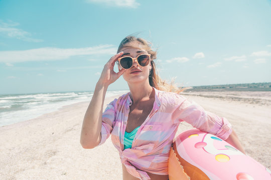 Girl relaxing on donut lilo on the beach