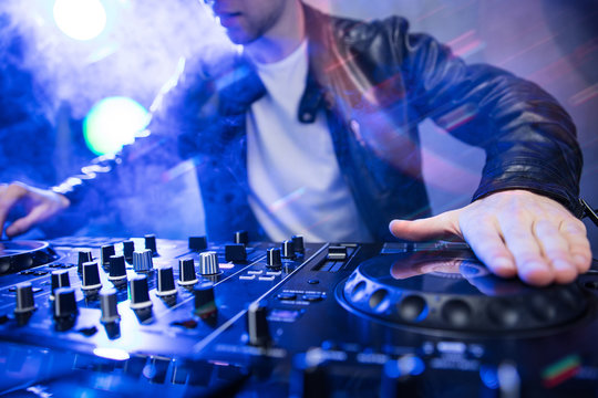 Dj mixing at party festival with red light and smoke in background - Summer nightlife view of disco club inside. Focus on hand
