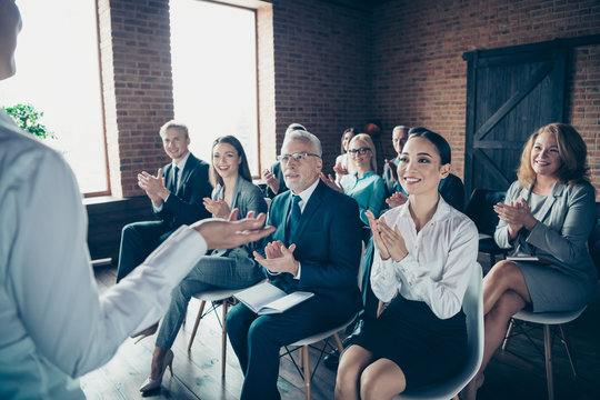 Crowd of nice cheerful trendy elegant specialists experts attending classes courses listening to coacher speaker economy clapping palms at industrial loft style interior work place station indoors