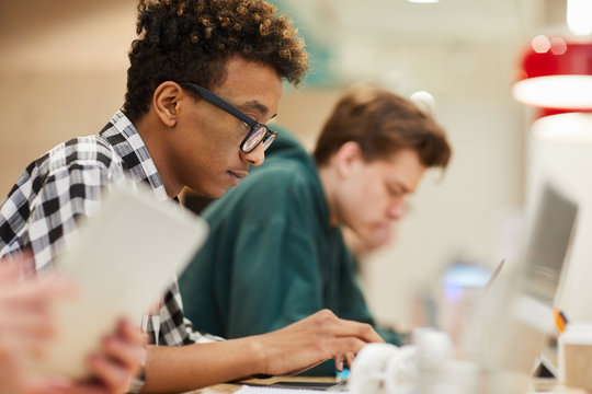 Serious concentrated black student in glasses concentrated on coding sitting at table and using laptop