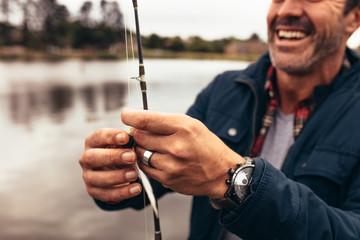 Close up of a man fishing near a lake