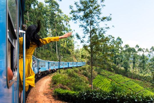 Woman enjoying train ride through Sri Lanka tea plantations