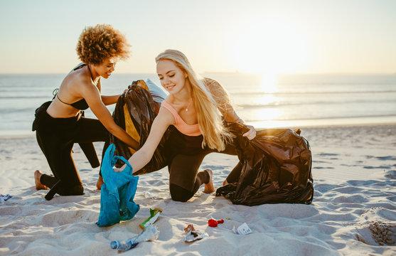 Women cleaning up a sandy beach