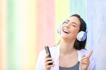 Happy girl singing listening to music in a colorful street