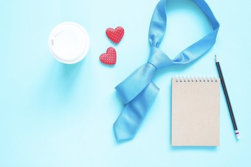 Creative flat lay of Father's Day concept. Necktie and notebook  on pastel colour background