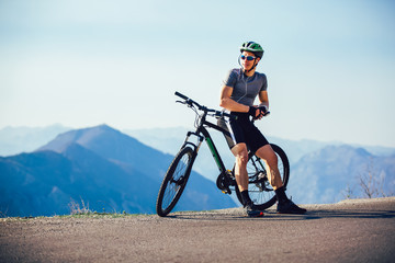 Athletic sportsman cyclist standing with bike enjoying beautiful view. Wall mural