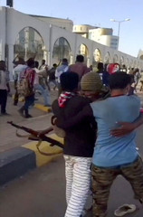 Still image taken from video showing person in military uniform embracing two protesters during a rally outside the defence ministry in Khartoum