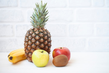 Diet weight loss breakfast concept with tape measure organic apple, orange, kiwi, grapefruit, bananas on a white background