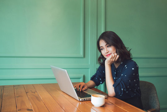 Beautiful cute asian young businesswoman in the cafe, using laptop and drinking coffee smiling