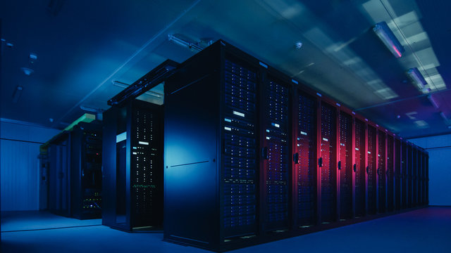 Shot of Data Center With Multiple Rows of Fully Operational Server Racks. Modern Telecommunications, Cloud Computing, Artificial Intelligence, Database. Shot in Dark with Neon Blue, Pink Lights.