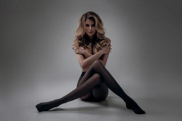 Beautiful sexy blonde girl posing topless in a studio in black pantyhose. advertising space