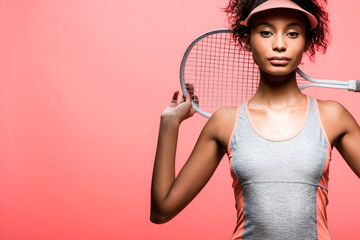 african american sportswoman in sun visor holding tennis racket and looking at camera isolated on coral with copy space