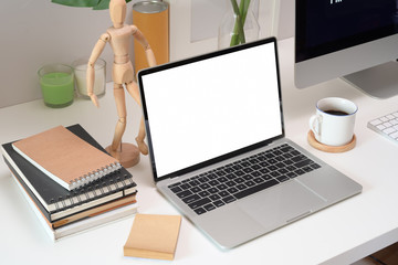 Mock up blank screen laptop in loft workspace.