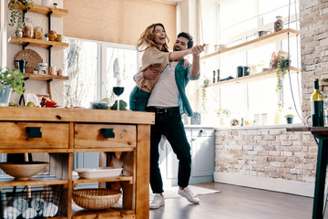 Playful. Full length of beautiful young couple in casual clothing dancing and smiling while standing in the kitchen at home