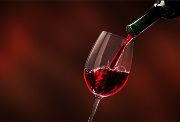 Red wine being poured in wineglass, closeup