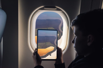 Caucasian boy using tablet pc for taking picture through plane window Salt Ponds in Don Edwards. San Francisco Bay National Wildlife Refuge. California. USA