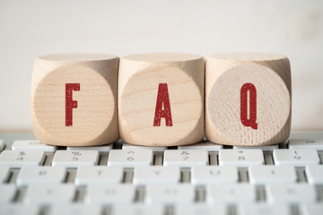 "cubes with acronym ""FAQ"" for frequently asked questions a keyboard"