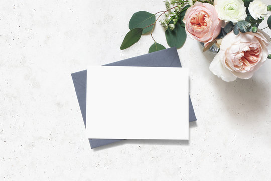Feminine wedding, birthday mock-up scene. Blank paper greeting card, envelope. Bouquet of eucalyptus leaves, blush pink English roses and ranunculus flowers. Concrete table background. Flat lay, top
