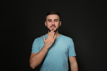 Man showing THANK YOU gesture in sign language on black background