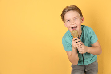 Cute boy singing in microphone on color background. Space for text