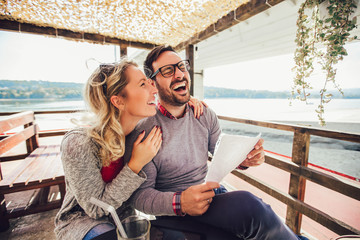 Young cheerful man and woman dating and spending time together in cafe