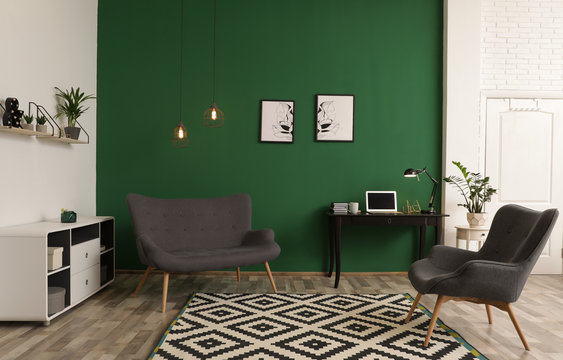Modern living room interior with workplace near green wall