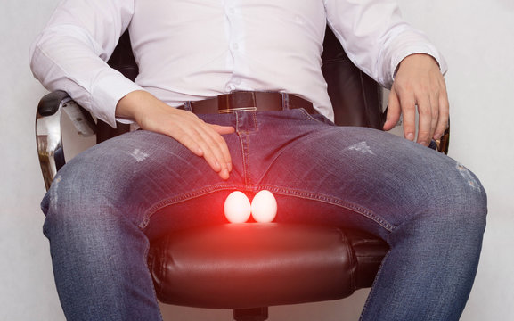 A man in a white shirt is sitting on a chair with a cyst of the epididymis of the scrotum, orchitis and inflammation, pain