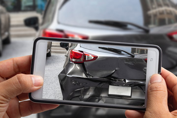 Car insurance agents take pictures of accident-damaged vehicles with a smartphone.