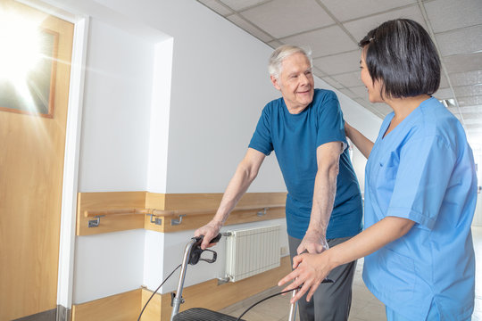 Asian female doctor reassuring mature elderly man with walker. Man and woman smiling happy in the hospital aisle. Retirement community concept