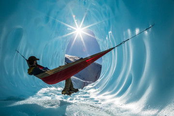 Sitting in a hammock inside the entrance of an ice cave in a glacier in Alaska.