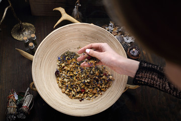 Herbalism, a woman prepares a healing mix of herbs.
