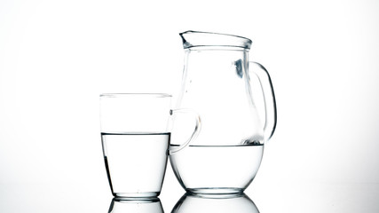 Jug and glass of water on white background