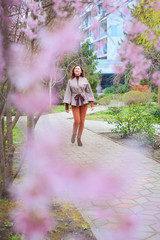Papiers peints Mermaid An attractive young woman with long hair walks in a spring Park on a background of flowering magnolias.