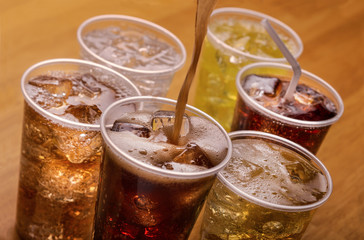 Plastic cups of varying types of carbonated drinks