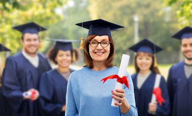 graduation, adult education and old people concept - happy senior graduate student woman in mortar board with diploma laughing over group of classmates in summer park background