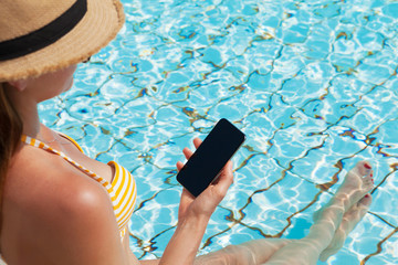 Young woman using smartphone near a swimming pool