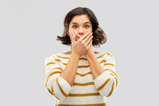 emotion, expression and people concept - shocked young woman in striped pullover covering her mouth by hands over grey background