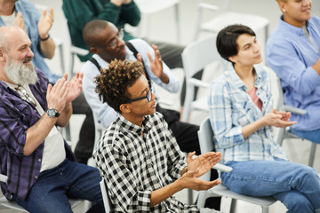 Audience of educational forum: group of content multi-ethnic people sitting on chairs and applauding for speaker at conference