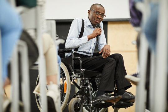 Serious confident motivational disabled mature African-American speaker in glasses sitting in wheelchair and looking at audience while saying speech into microphone at conference