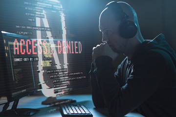 cybercrime, hacking, wiretapping and technology concept - male hacker in headphones with access denied message on computer screen using virus program for cyber attack in dark room - fototapety na wymiar