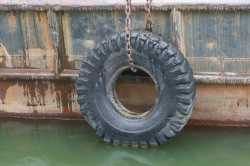 The image of the riverboat hull. Automobile tire provides secure mooring.
