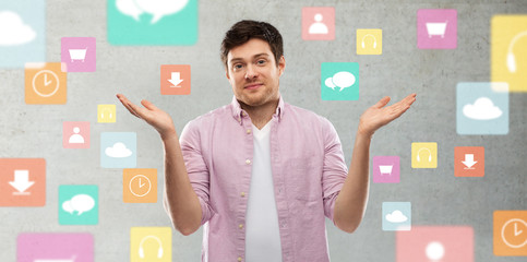 people, technology and expression concept - young man shrugging over app icons on grey background