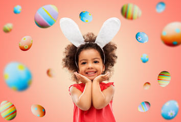 easter, holidays and childhood concept - happy little african american girl wearing bunny ears headband posing over living coral background and colored eggs
