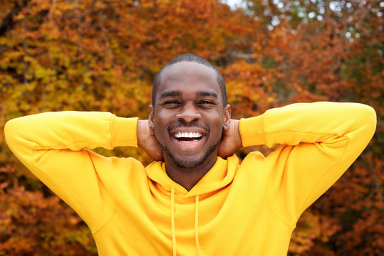 handsome young african american man smiling with autumn leaves in background and hands behind head