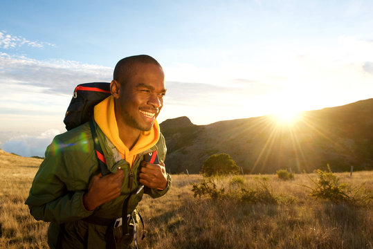 young black man walking with backpack in mountains with sunrise in background