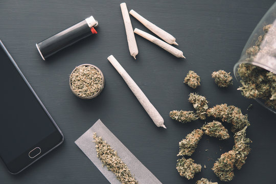 grinder in hand with fresh marijuana, joint with weed, Cannabis buds on black table, close up,