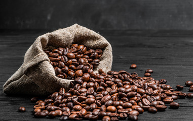 Wall Murals Coffee beans Organic coffee seeds scattering from the sack over the dark wooden surface. Fresh coffee beans near the light brown sack isolated. Close-up