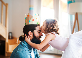A side view of small girl with a princess crown and young father at home, playing.
